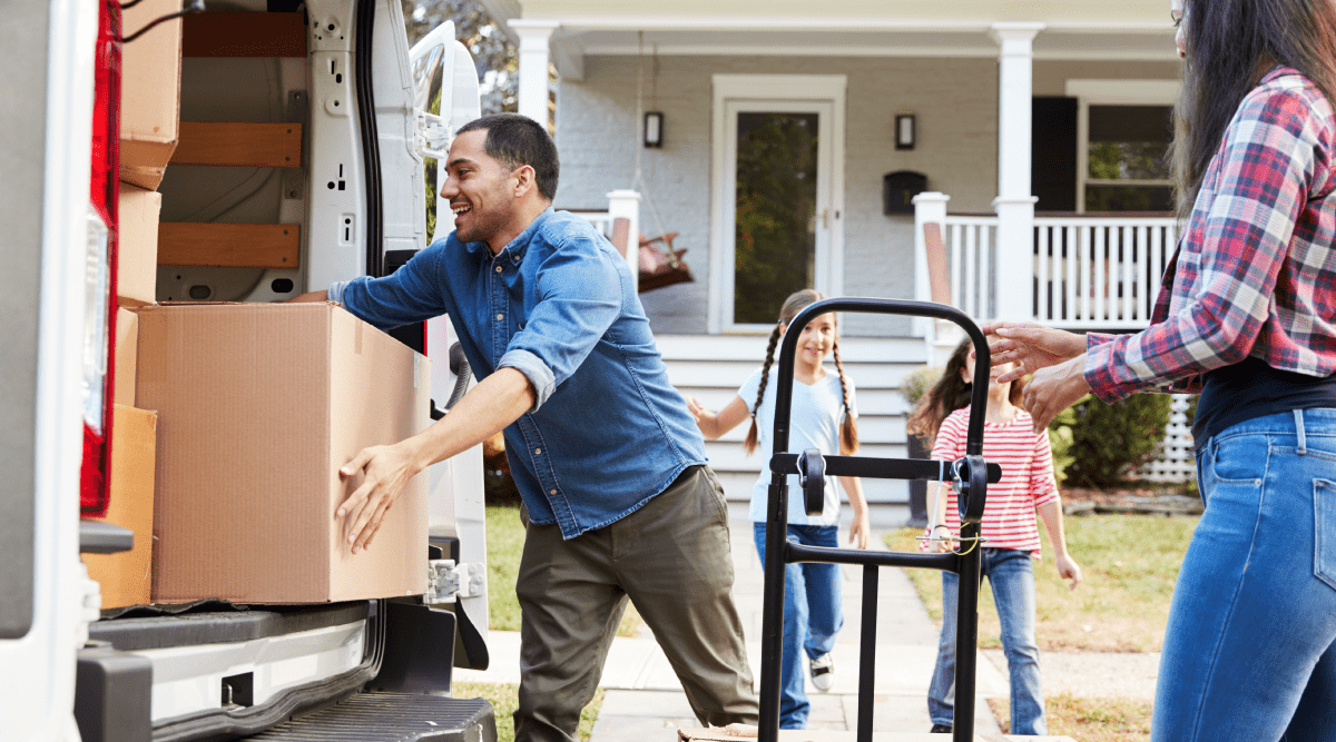 Family moving boxes into moving truck